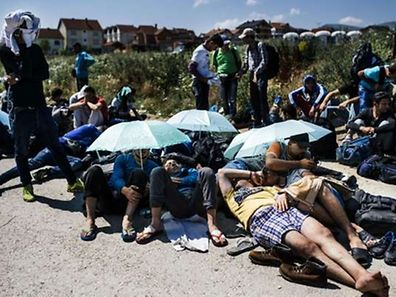 Migrants sitting and resting close to the  police station in the southern Serbian town of Presevo, near the border with Macedonia