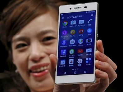 A model poses with Sony's new Xperia Z4 smartphone after a news conference in Tokyo April 20, 2015. Sony Corp on Monday unveiled the new high-end Xperia handset featuring an aluminium frame and a 5.2-inch screen, showing it is still in the smartphone race even as it scales down its struggling mobile operations.    REUTERS/Toru Hanai
