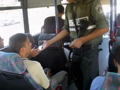 Israeli border policeman check the IDs of bus passengers