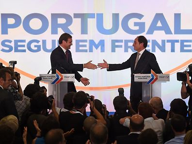 Social Democratic Party (PSD) leader and Portuguese Prime Minister Pedro Passos Coelho (L) and coalition leader of the Popular Party Paulo Portas congratulate each other at the end of their joint press conference in Lisbon after winning the general elections on October 4, 2015. The leader of Portugal's opposition Socialists, former Lisbon mayor Antonio Costa, conceded today defeat in a general election billed as a referendum on four years of harsh austerity policies, as near-complete results gave the ruling centre-right coalition a clear lead.   AFP PHOTO/ FRANCISCO LEONG