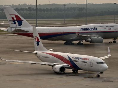 A Malaysia Airlines Boeing-737 plane taxis past a 747