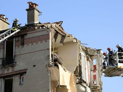Firefighters use a crane and a ladder to inspect a building adjacent to a four-storey residential building that collapsed following a blast in Rosny-sous-Bois in the eastern suburbs of Paris on August 31, 2014. Local authorities have not yet determined what caused the blast that led to the collapse, killing a child and wounding 11 people.  AFP PHOTO / BERTRAND GUAY