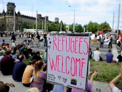 """An anti-racism protesters sit behind a banner with the lettering """"Refugees Welcome"""" during a rally on August 29, 2015 in Dresden, stronghold of the anti-Islam PEGIDA movement, whose demonstrations drew up to 25,000 at the start of the year. Activists demonstrate in solidarity with migrants, in a show of defiance against far-right extremists who have mounted noisy protests against a record influx of migrants to Germany. AFP PHOTO / ROBERT MICHAEL"""