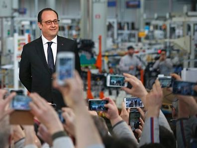 Employees take pictures with their mobile phone as French President Francois Hollande waits to deliver a speech after a visit at the French carmaker PSA Peugeot Citroen engine factory in Tremery near Metz, North Eastern France, March 27, 2015. PSA Peugeot Citroen said on Friday it had chosen a French factory over a rival Spanish plant to expand engine production. The troubled carmaker said it will upgrade the Tremery site to produce the turbo version of a staple three-cylinder engine already manufactured there, safeguarding local jobs.   REUTERS/Vincent Kessler TPX IMAGES OF THE DAY