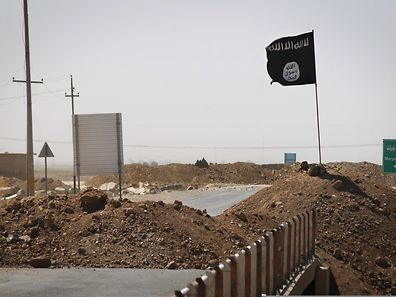 A flag of the Islamic State (IS) is seen at the frontline of fighting between Kurdish Peshmerga fighters and Islamist militants in Rashad, Iraq