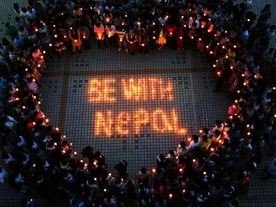 This picture taken on April 26, 2015 shows Nepalese students and Chinese students gathering to pray for Nepal in Nanhua University in Hengyang, central China's Hunan province. International rescue teams and relief supplies began arriving in Nepal's devastated capital on April 27 to help terrified and homeless survivors of a quake that has killed more than 3,200 people in the impoverished nation. CHINA OUT AFP PHOTO