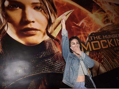 """Eine thailändische Studentin zeigt vor einem der Filmplakate den """"Dreifinger-Gruß"""", das inoffizielle Symbol der Protestbewegung."""