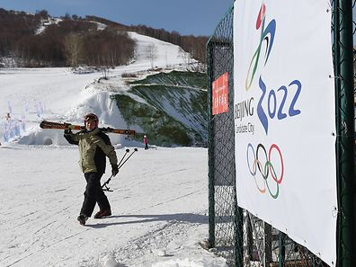 This picture taken on January 17, 2015 shows a man walking past a billboard after skiing at the Yunding Ski Field in Chongli town, near the Zhangjiakou,in China's Hebei Province.  A flag on a barren mountainside marks where China hopes ski jumpers will vault to glory at the Winter Olympics.