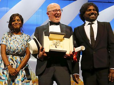"Director Jacques Audiard (C), Palme d'Or award winner for his film ""Dheepan"", actress Kalieaswari Srinivasan and actor Jesuthasan Antonythasan pose on stage during the closing ceremony of the 68th Cannes Film Festival in Cannes, southern France, May 24, 2015.                       REUTERS/Regis Duvignau"
