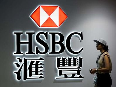 A woman walks past a logo of the HSBC bank in Hong Kong on August 3, 2015. Banking giant HSBC was to release its six-month financial results on August 3, 2015.  AFP PHOTO / Philippe Lopez