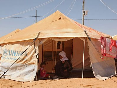 A refugee woman from sits with a child inside a tent at the khanki refugee camp on the outskirts of Dohuk province