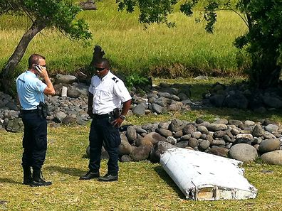A policeman and a gendarme stand next to a piece of debris from an unidentified aircraft found in the coastal area of Saint-Andre de la Reunion, in the east of the French Indian Ocean island of La Reunion, on July 29, 2015.  The two-metre-long debris, which appears to be a piece of a wing, was found by employees of an association cleaning the area and handed over to the air transport brigade of the French gendarmerie (BGTA), who have opened an investigation. An air safety expert did not exclude it could be a part of the Malaysia Airlines flight MH370, which went missing in the Indian Ocean on March 8, 2014. AFP PHOTO / YANNICK PITON