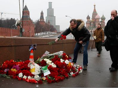 People come to lay flowers at the site, where Boris Nemtsov was shot dead, with St. Basil's Cathedral (R) and the Kremlin walls seen in the background, in central Moscow