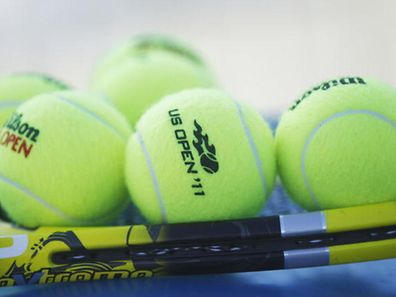 Tennis balls and a racket are shown near a court during the U.S. Open tennis tournament in New York, Thursday, Sept. 1, 2011. (AP Photo/Julio Cortez)