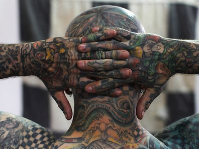 "Matt Gone, also known as ""The Checkered Man"" poses during the GuateMayan Tattoo Convention in Guatemala City July 19, 2014. Gone claims to be one of the most tattooed people in the world, with 98 percent of his body inked.     REUTERS/Jorge Dan Lopez (GUATEMALA - Tags: SOCIETY)"