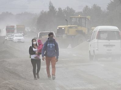 Residents wearing surgical masks to protect themselves against ash from Calbuco volcano, walk in a street in Ensenada, Chile April 26, 2015.