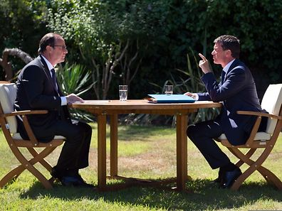 File picture taken on August 15, 2014 shows French President Francois Hollande (L) and French Prime Minister Manuel Valls speaking during a work meeting  at the Fort de Bregancon