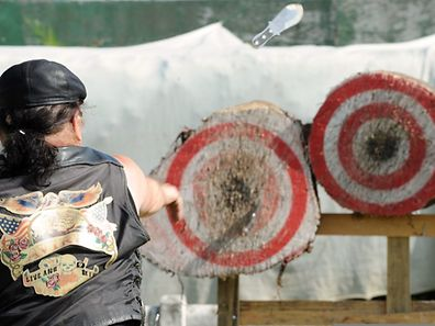 A man throws a knife towards a target August 23, 2014 as he competes in the knives and hatchets throwing world championships in Callac,  western France.
