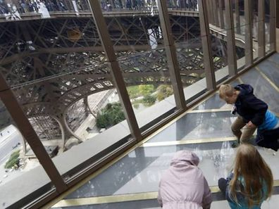 Visitors stand on the new glass floor at the Eiffel Tower in Paris October 6, 2014