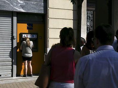 Les gens se massent derrière les distributeurs de billets alors que les liquidités vont cesser d'affluer vers la Grèce.