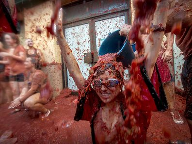"""A reveller has a bucket of tomato pulp emptied over her during the annual """"tomatina"""" festivities in the village of Bunol, near Valencia on August 26, 2015. Some 22,000 revellers hurled 150 tonnes of squashed tomatoes at each other drenching the streets in red in a gigantic Spanish food fight marking the 70th annual """"Tomatina"""" battle.    AFP PHOTO / BIEL ALINO"""