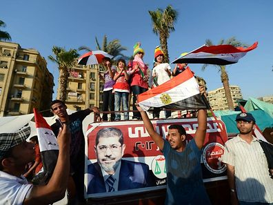 Egyptians celebrate on June 24, 2012, in Cairo's Tahrir Square the victory of Muslim Brotherhood member Mohamed Morsi (poster) who was declared the first president of Egypt since a popular uprising ousted Hosni Mubarak