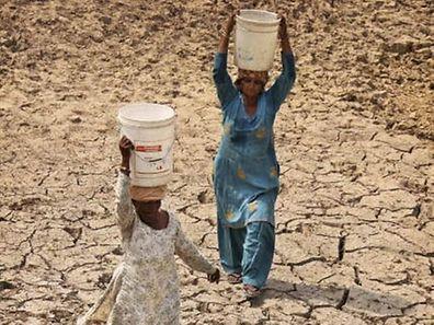 Frauen in Indien tragen Behälter mit Wasser.