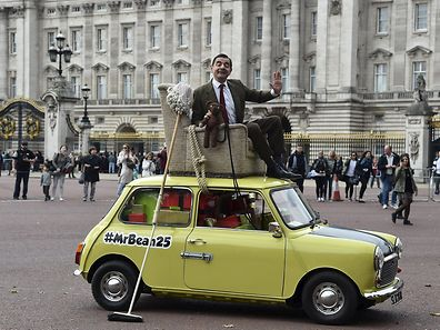 British comedian Rowan Atkinson, in character as 'Mr Bean', poses on a Mini car besides Buckingham Palace in central London, September 4, 2015.  He was promoting the television and film comedy character Mr Bean. REUTERS/Toby Melville
