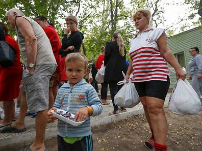 Ukrainian refugees from the Donetsk region receive food as humanitarian aid on the outskirts of the southern coastal town of Mariupol September 10, 2014