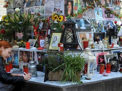 A woman kneeling besides flowers, letters and pictures of US singer Michael Jackson which are fixed on a monument dedicated to Franco-Flemish Renaissance composer Orlando di Lasso in Munich, southern Germany. Authorities in the southern German city, say in July 2015 the memorial may have to go to keep the peace as rival factions have entered into a bitter battle