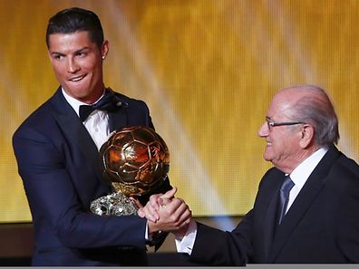 Real Madrid's Cristiano Ronaldo of Portugal is congratulated by FIFA President Sepp Blatter (r.) after winning the FIFA Ballon d'Or