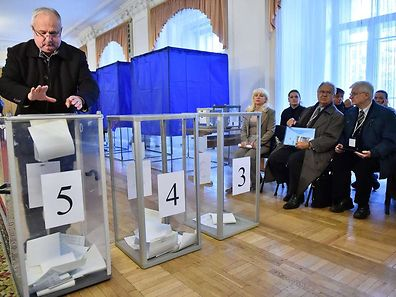 Observers watch as a man casts his ballot in a polling station in Kiev on October 26, 2014