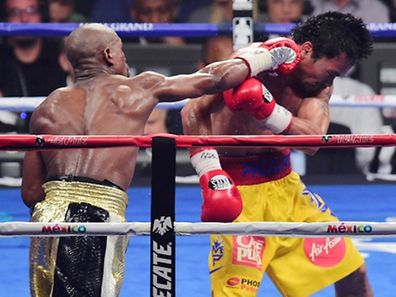 Floyd Mayweather (black/gold trunks) and Manny Pacquiao (yellow/red trunks) box during their world welterweight championship bout at MGM Grand Garden Arena