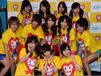 Nine Japanese porn actresses, (middle L-R) Kotone Nishida, Iku Sakuragi, Rina Serino, Yui Kasugano and Nodoka Otsuka, (rear L-R) Yuria Kitahara, Riku Nekota, Yumena Muro and Karin Natsumi, pose with three supporters (front) in Tokyo