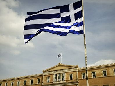 A Greek flag flies by the Greek Parliament in Athens