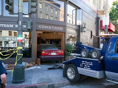 A tow truck stands parked  after a car (C) crashed into a bar in San Francisco, California on Monday, September 15, 2014, leaving three people injured.  The driver, whose name was not immediately released, reportedly  lost control of the vehicle, remained on the scene, cooperated with police, and was then arrested on an outstanding $250,000 warrant for the sale of narcotics, police said.    AFP PHOTO / JOSH EDELSON