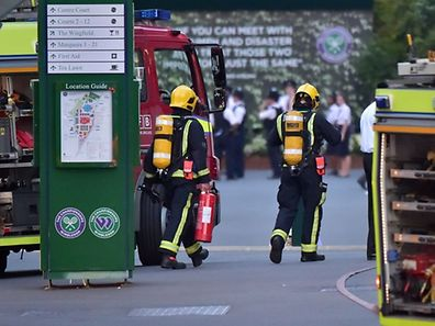 Fire crews in breathing aparatus walk towards Centre Court  following a fire alert and evacuation on day three of the 2015 Wimbledon Championships at The All England Tennis Club in Wimbledon, southwest London, on July 1, 2015.   RESTRICTED TO EDITORIAL USE  --   AFP PHOTO / JUSTIN TALLIS