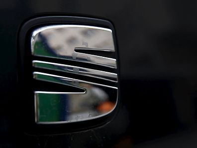 A woman is reflected on the logo of Spanish automaker SEAT in Barcelona, Spain, September 29, 2015. About 700,000 of the 11 million diesel engines involved in the Volkswagen emissions scandal were manufactured by the company's brand Seat, a spokesman for the Spanish unit said on Tuesday. REUTERS/Sergio Perez
