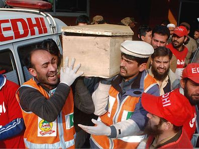 Rescue workers and family members carry the coffin of a student, killed during an attack by Taliban gunmen on the Army Public School in Peshawar