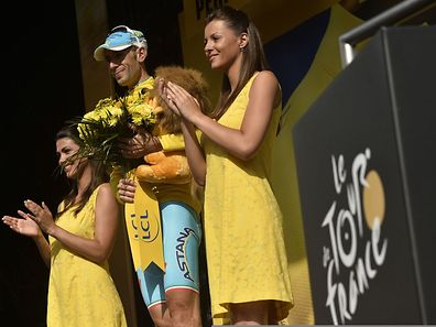 Italy's Vincenzo Nibali celebrates his overall leader yellow jersey on the podium at the end of the 20h stage