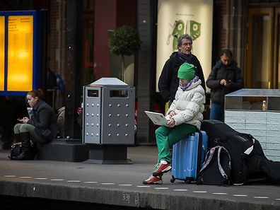 Travellers wait at the Central Station of Amsterdam, on March 27, 2015 during a major power outage. Large parts of North Holland, including neighborhoods in Amsterdam are without electricity. The error affects the traffic, trains, the Dutch Media Park in Hilversum and Schiphol Airport.  AFP PHOTO/ANP/REMKO DE WAAL - NETHERLANDS OUT