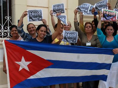 Cubans celebrate with a national flag in Camaguey, 600 km east of Havana on December 17, 2014, after Washington released three Cuban spies