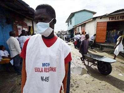 A health ministry employee visits the West Point district in Monrovia as part of an awareness campaign for Ebola on October 2, 2014.