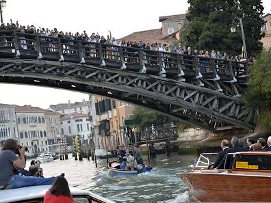 "People wave from a bridge to US actor George Clooney standing on a taxi boat on the Grand Canal on his way to the Aman hotel on September 27, 2014 in Venice where Clooney and British fiancee, Amal Alamuddin celebrate their wedding. George Clooney has said goodbye to bachelorhood in Venice with a stag party at his favourite restaurant with Hollywood chums, and was gearing up for a day of glamourous pre-wedding celebrations. The actor had swept into the floating city yesterday with his British fiancee Amal Alamuddin on a watertaxi dubbed ""Amore"", zipping up the Grand Canal to cheers from fans at the start of nuptials set to draw out over the weekend.    AFP PHOTO / ANDREAS SOLARO"