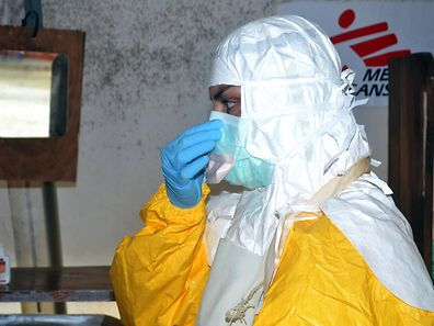 A member of Doctors Without Borders (MSF) puts on protective gear at the isolation ward of the Donka Hospital in Conakry