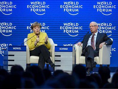A chanceler alemã Angela Merkel ao lado de um dos fundadores do Fórum Económico Mundial, Klaus Schwab