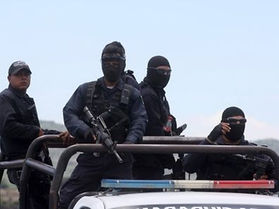 Federal police officers leave the ranch where gunmen took cover during an intense gun battle with the police, along the Jalisco-Michoacan highway in Vista Hermosa, Michoacan State, on May 22, 2015. At least 37 people were killed in the gunfight in Mexico's troubled western state of Michoacan, in one of the bloodiest clashes in the country's drug war. Two police officers also died in the shootout in the municipality of Tanhuato, near the border with Jalisco state, a federal government official told AFP. Michoacan and Jalisco have endured some of the worst violence in a drug war that began to escalate in 2006, when the government deployed troops to combat cartels. More than 80,000 have been killed and another 22,000 gone missing nationwide in the past nine years.  AFP PHOTO / HECTOR GUERRERO