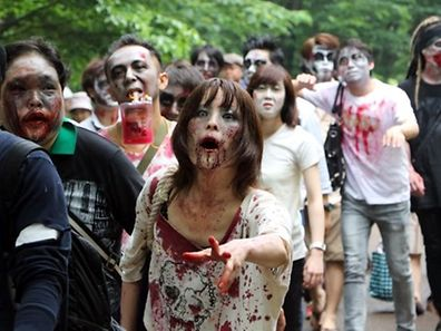 "Participants take part in a 'zombie walk' at a park in Tokyo on May 16, 2015. Some 100 zombie maniacs flocked to a Tokyo park for an annual gathering, dressing in ""bloodstained"" costumes with grisly gore makeup. AFP PHOTO / Yoshikazu TSUNO"