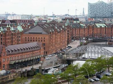 FILES - Picture taken on May 27, 2015, shows the Speicherstadt historic warehouse district and the construction site of the Elbphilharmonie Philharmonic Hall in Hamburg, northern Germany. The historic warehouse district Speicherstadt in Hamburg has been included in the prestigious UNESCO list of world heritage sites as the organization's committee in Bonn, western Germany, decided on July 5, 2015.  AFP PHOTO / DPA / DANIEL BOCKWOLDT +++ GERMANY OUT