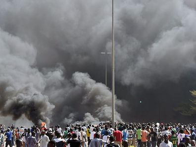 People stand in front of smoke rising from the Burkina Faso's Parliament, where demonstrators set cars on fire parked in a courtyard of the Parliament